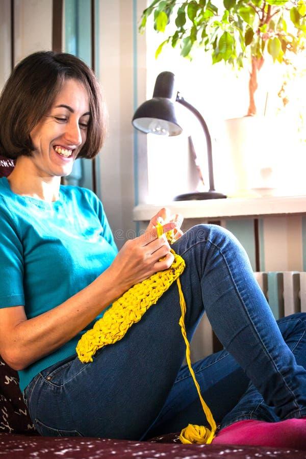 Mädchen strickt Häkelarbeit zu Hause Frau teilgenommen an Näharbeit Ein Stricker sitzt auf einem Sofa und Arbeiten Kreatives Hobb stockbilder