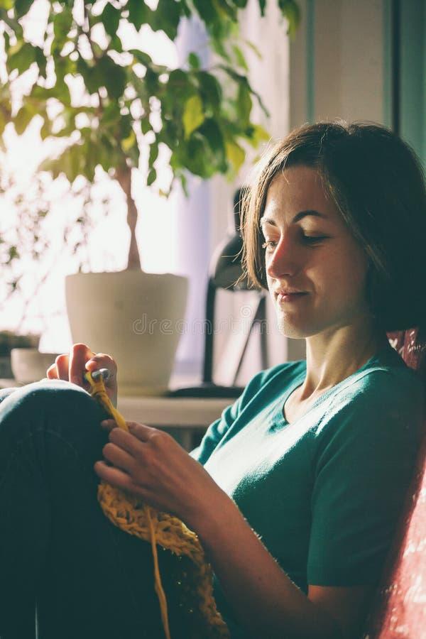 Mädchen strickt Häkelarbeit zu Hause Frau teilgenommen an Näharbeit Ein Stricker sitzt auf einem Sofa und Arbeiten Kreatives Hobb stockfotografie