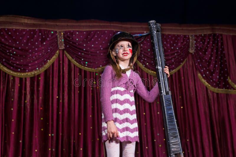 Mädchen-tragender Sturzhelm, der Gewehr aufrecht auf Stadium hält stockfotos
