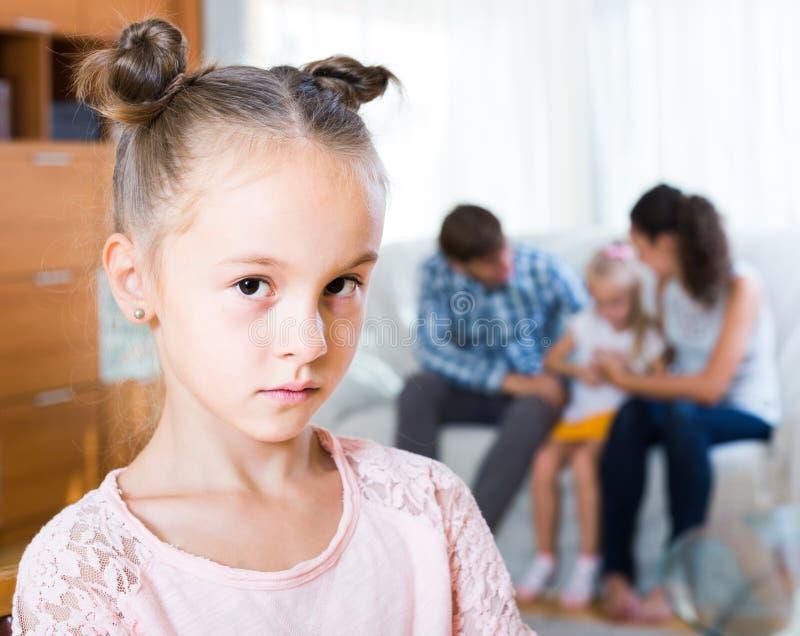 Mädchen traurig wegen der eifersüchtigen jüngeren Schwester zu den Eltern lizenzfreie stockfotografie