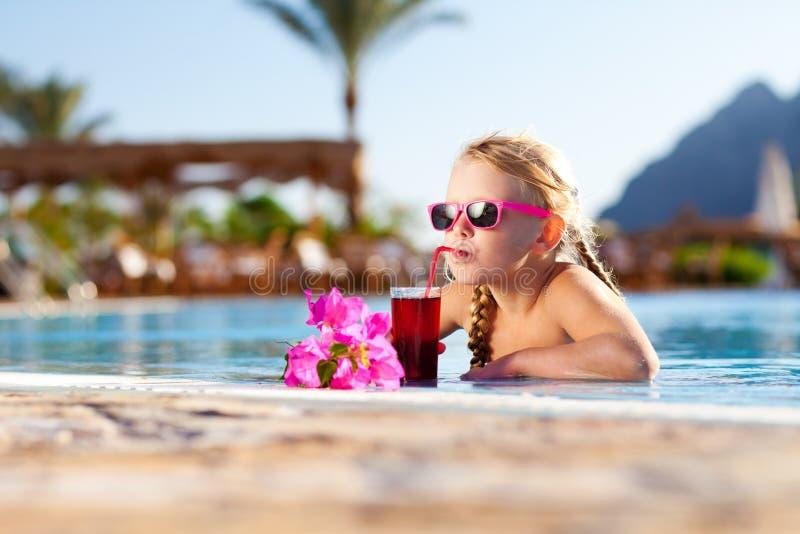 Mädchen trinkendes coctail im Pool lizenzfreie stockfotos