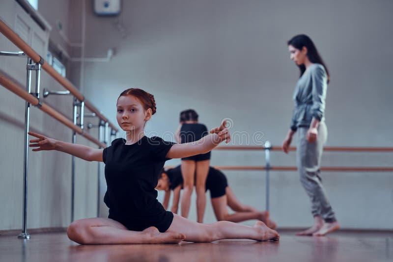 Mädchen tut das Strechening während ihre anderen Mitschüler, die Übungen mit Lehrer tun stockfoto
