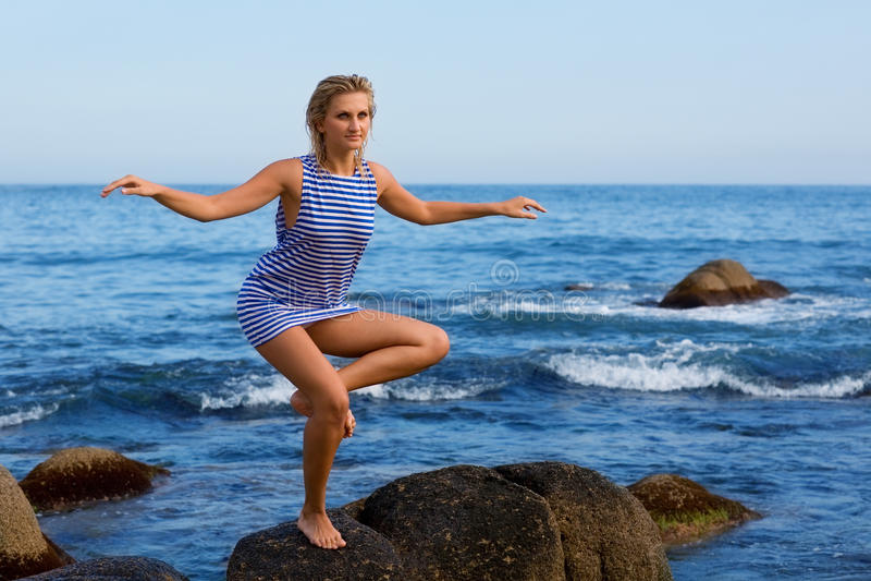 Mädchen tut Yogaübungen durch Meer lizenzfreie stockfotografie