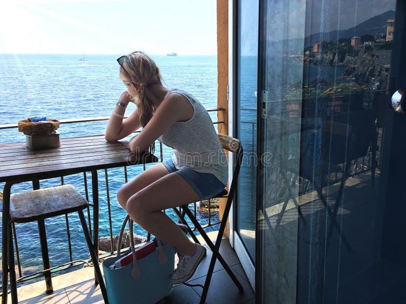 Mädchen-Uhrmeer vom Balkon lizenzfreies stockbild