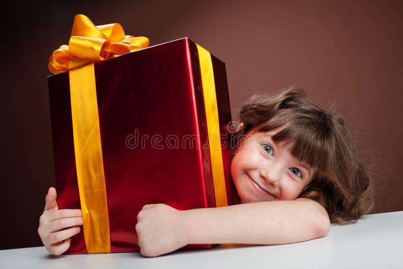 Mädchen umfaßt fröhlich das Geschenk stockbild