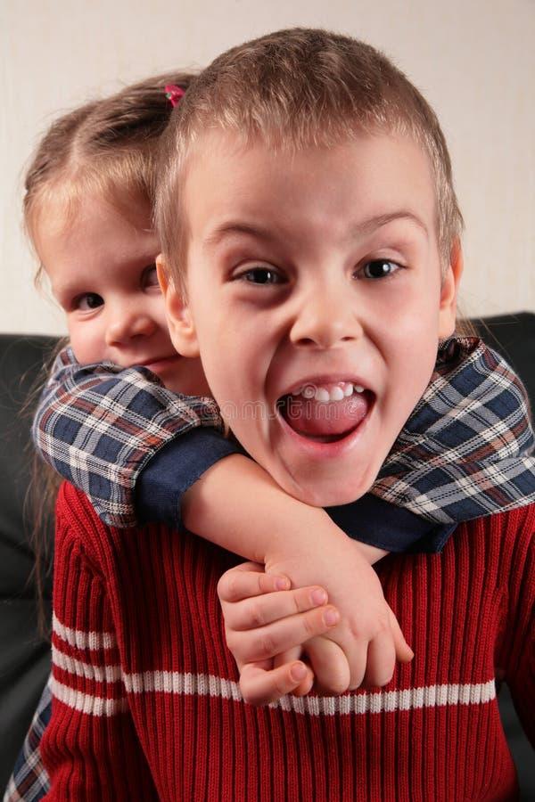 Mädchen umfaßt Jungen für den Stutzen, stockfoto