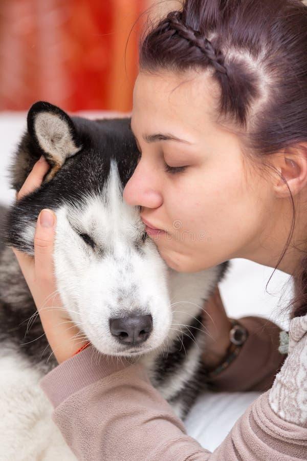 Mädchen umfasst einen Hund des sibirischen Huskys lizenzfreie stockbilder
