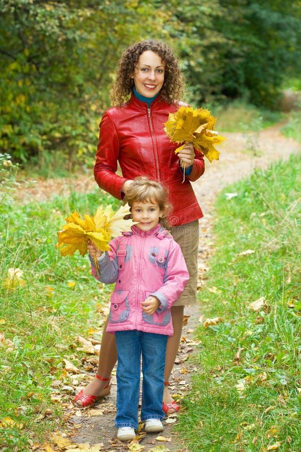 Mädchen und Frau mit Ahornblättern im Park im Herbst lizenzfreie stockbilder
