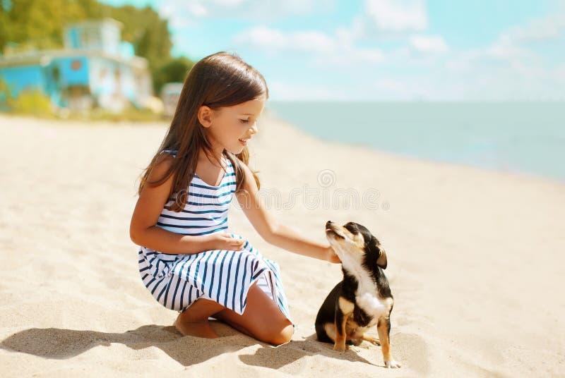 Mädchen und Hund auf dem Strand stockfoto