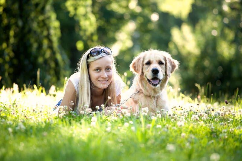 Mädchen und Hund im Gras lizenzfreie stockfotografie