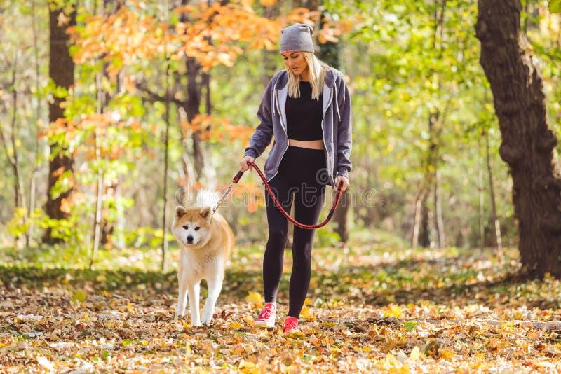 Mädchen und ihr Hund, die in Park gehen lizenzfreie stockfotos