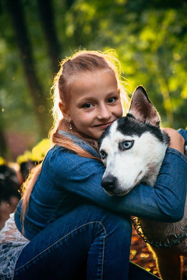 Mädchen und ihr Hundeschlittenhund auf dem Hintergrund von Blättern im Frühjahr lizenzfreie stockbilder