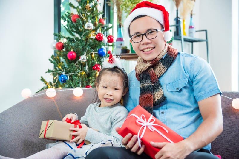 Mädchen und ihr Vater, die auf Sofa mit Weihnachtsgeschenkboxen sitzen lizenzfreie stockfotografie