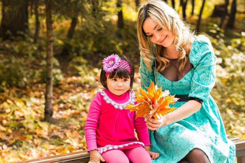 Mädchen und ihre Mutter, die draußen mit herbstlichen Ahornblättern spielen Baby, das goldene Blätter auswählt stockbilder