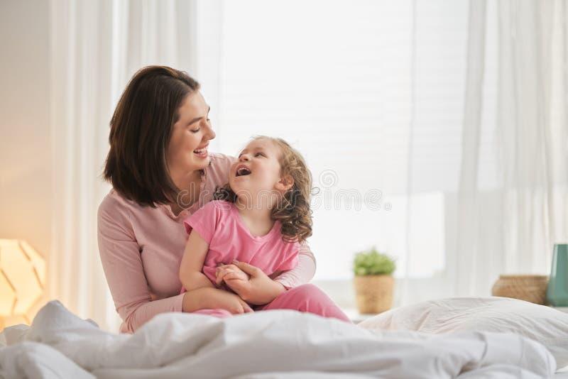 Mädchen und ihre Mutter genießen sonnigen Morgen lizenzfreie stockfotos