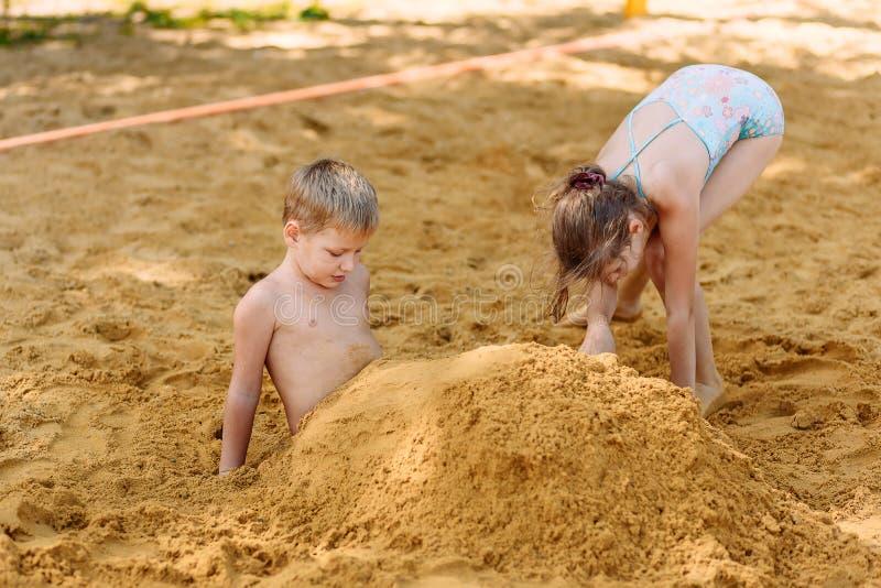 Mädchen und Junge in Badeanzügen ihre Füße im Sand auf dem Strand im Sommer begraben stockbilder