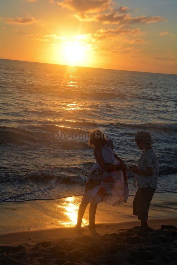 Mädchen und Junge bei dem Sonnenuntergang auf dem Strand lizenzfreie stockbilder