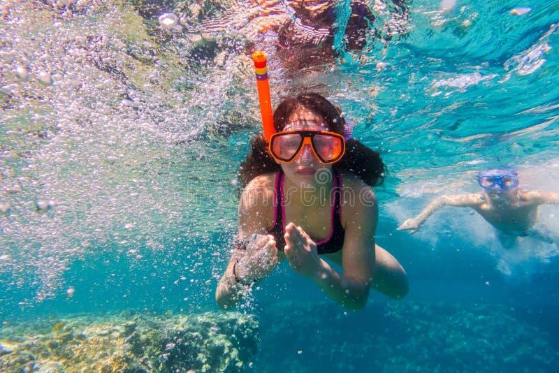 Mädchen und Junge in der Schwimmenmaske tauchen im Roten Meer nahe Korallenriff stockfotos