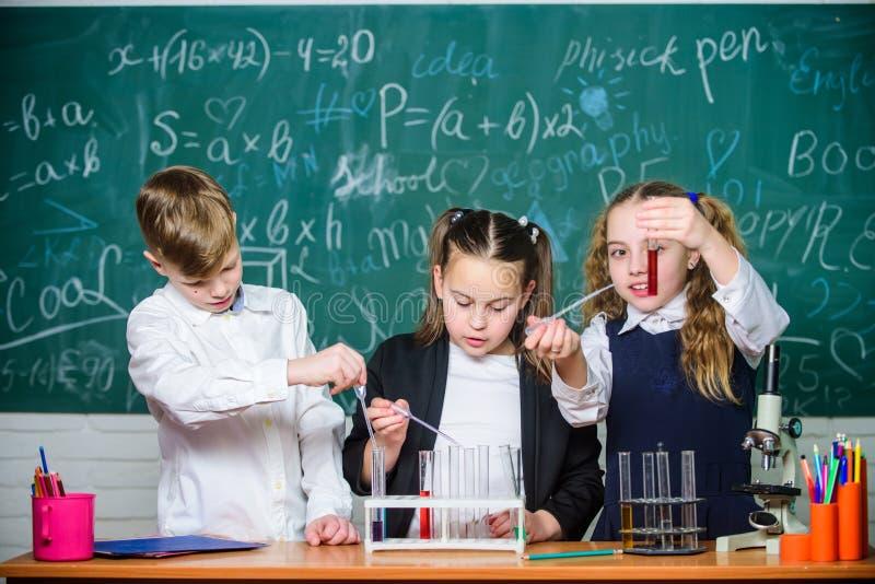 Mädchen und Junge, die Experiment mit Flüssigkeiten versehen Reagenzgl?ser mit bunten fl?ssigen Substanzen Studie von fl?ssigen Z lizenzfreies stockbild