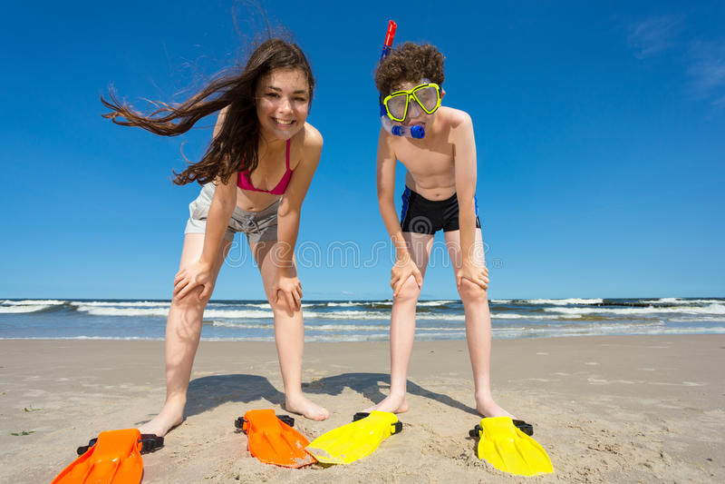 Mädchen und Junge, die Spaß auf dem Strand haben lizenzfreie stockbilder