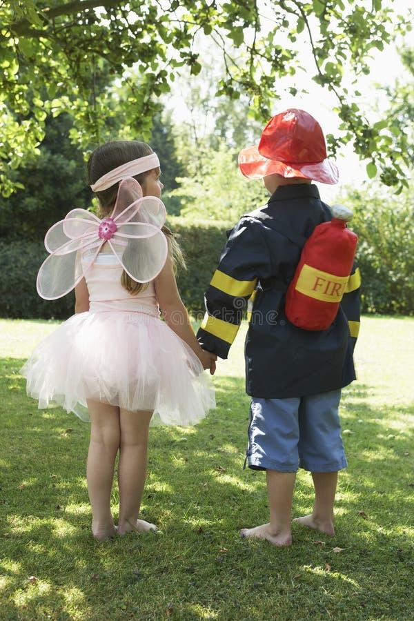 Mädchen und Junge gekleidet als Fee und Feuerwehrmann lizenzfreies stockfoto