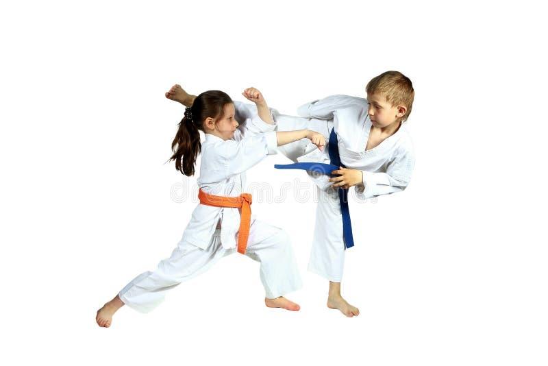 Mädchen und Junge im karategi bilden zusammengepaßtes Übungskarate aus stockfotos