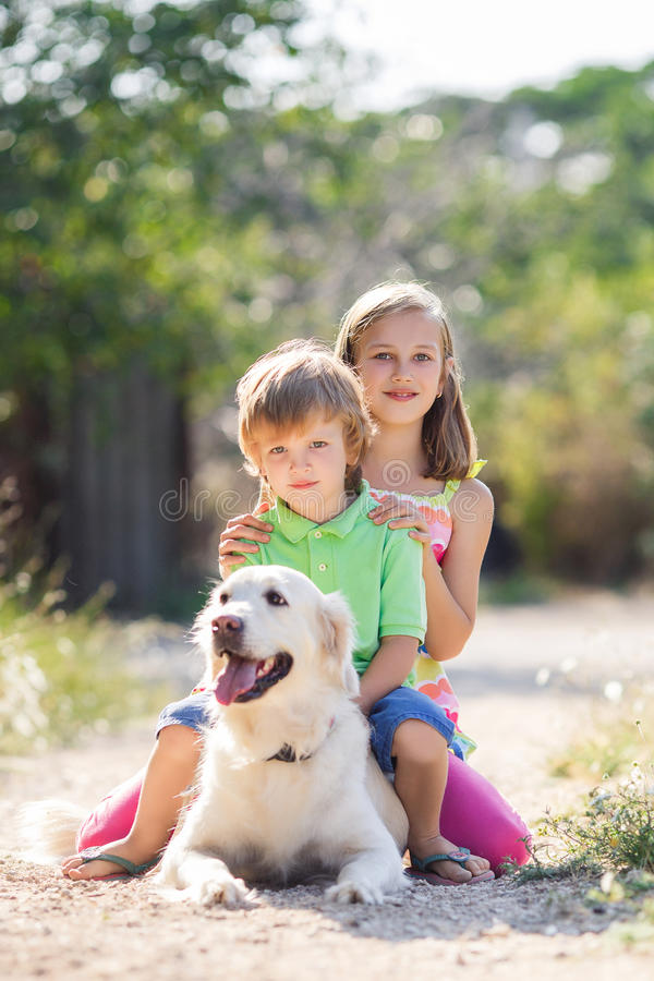 Mädchen und Junge mit einem großen Hund in einem Park im Sommer stockfotos