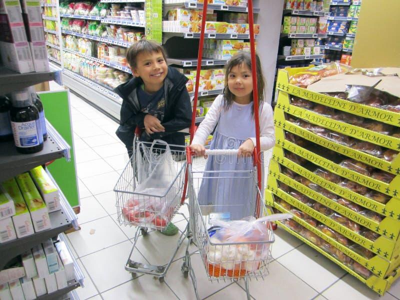 Mädchen und Junge am Supermarkt lizenzfreie stockfotografie