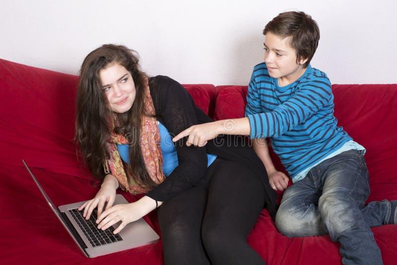 Mädchen und Junge und ein Laptop stockbild