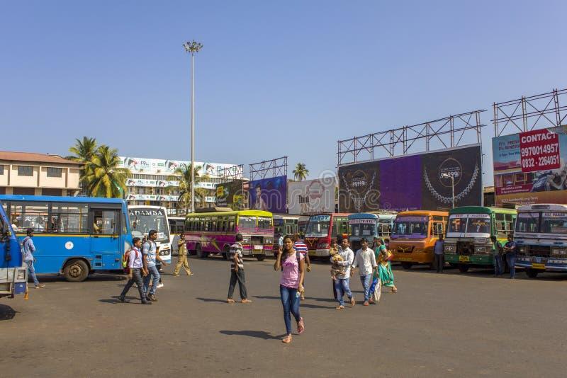 Mädchen und Jungen gehen in den Hintergrund parkten helle bunte Busse am Busbahnhof lizenzfreie stockfotografie