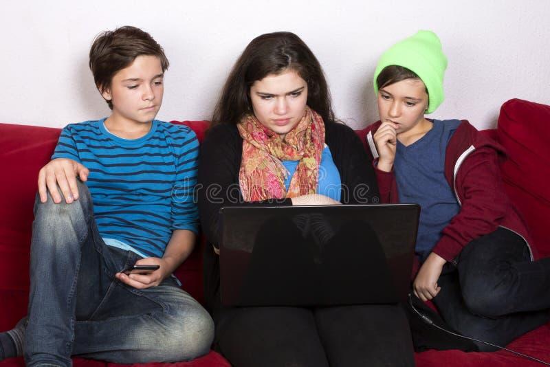 Mädchen und Jungen und ein Laptop stockfotos