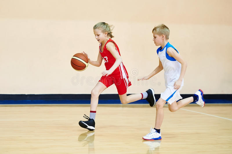 Mädchen- und Jungenathlet in der Uniform, die Basketball spielt lizenzfreie stockfotografie