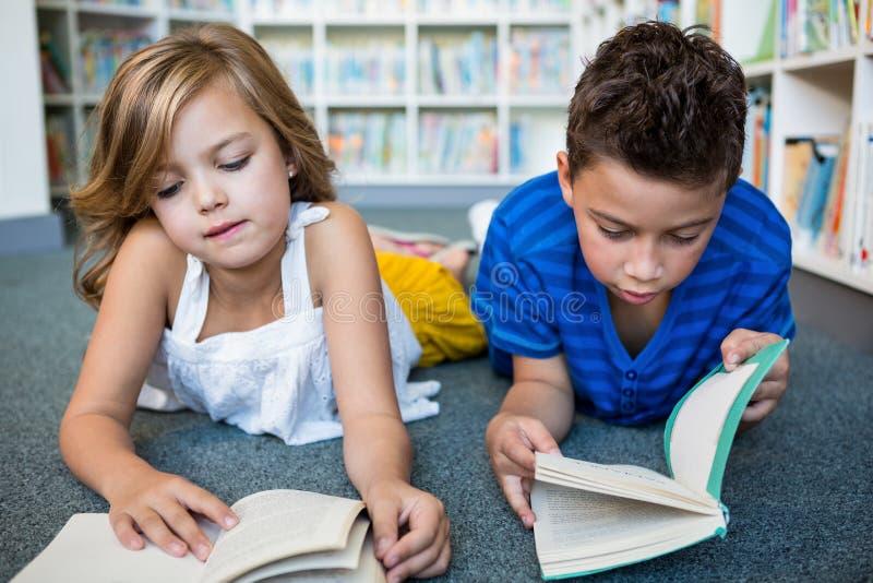 Mädchen- und Jungenlesebücher an der Bibliothek in der Schule stockfotografie