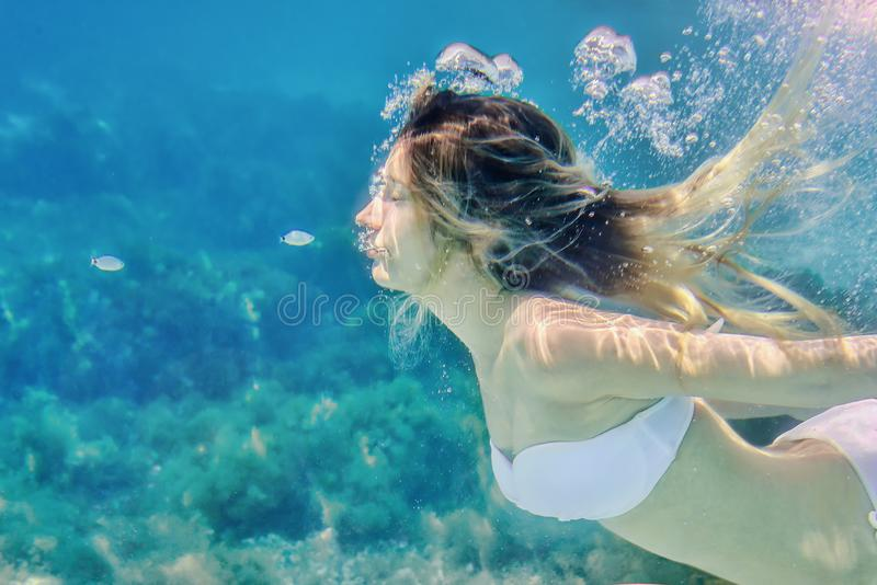 Mädchen und kleine Fische, die Unterwasserporträt schwimmen Hintergrund des blauen Wassers des Seesommers mit Blasen lizenzfreies stockfoto