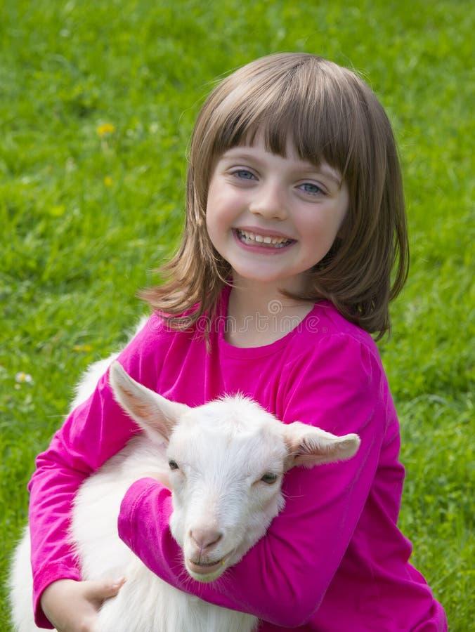 Mädchen und kleine Ziege, die auf einer Wiese sitzen lizenzfreie stockfotografie