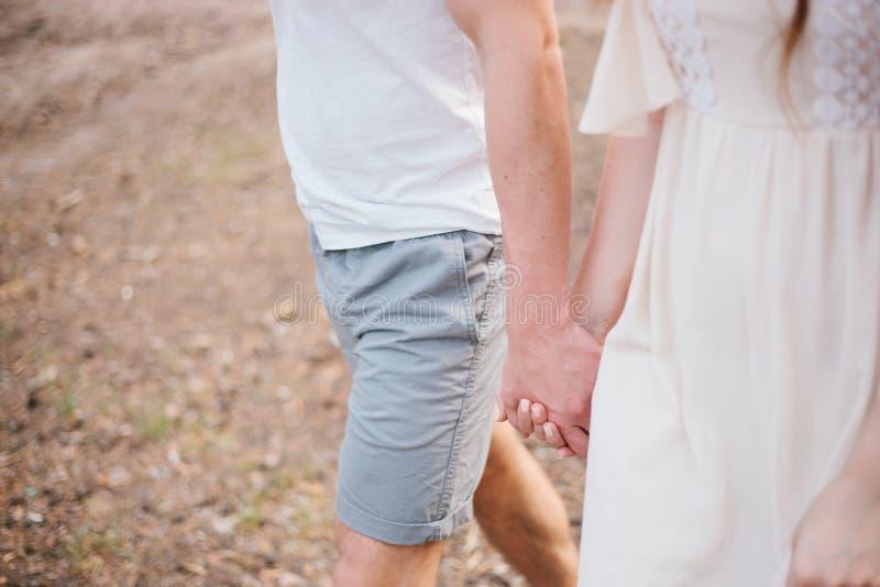 Mädchen- und Mannhändchenhalten, das durch den Wald geht stockbilder
