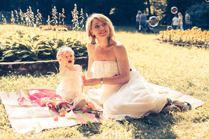 Mädchen und Mutter, welche die Seifenblasen durchbrennen lizenzfreie stockbilder
