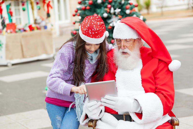 Mädchen und Santa Claus Using Digital Tablet lizenzfreie stockbilder