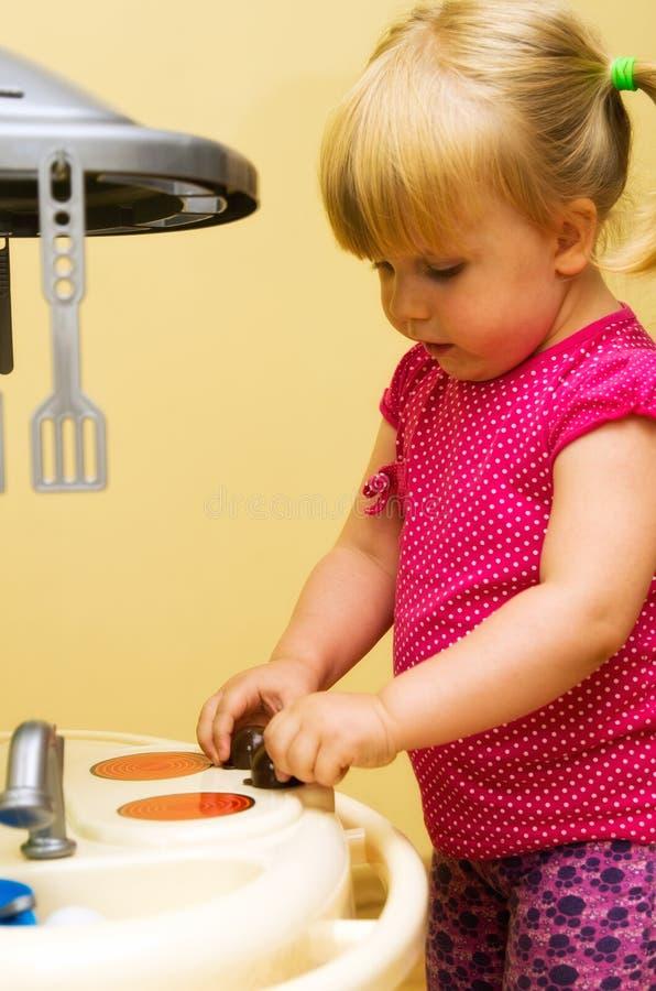 Mädchen- und Spielzeugküche stockfotos