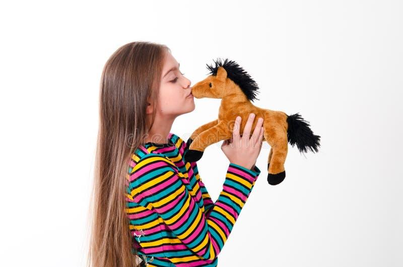 Mädchen- und Spielzeugpferd stockbilder