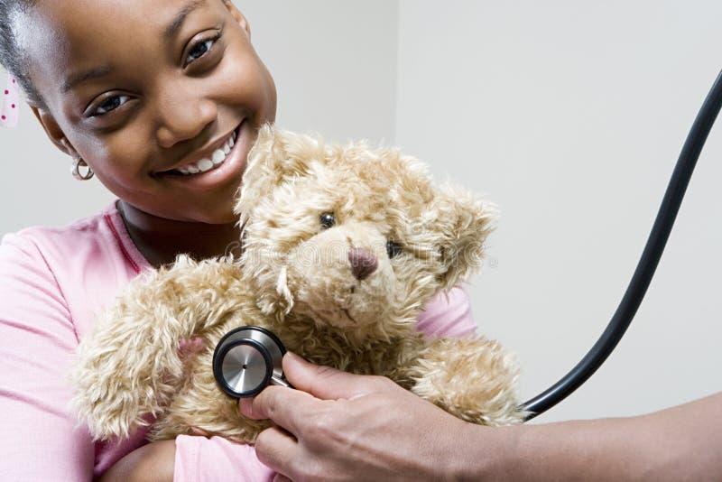 Mädchen und Teddybär mit Stethoskop lizenzfreies stockbild