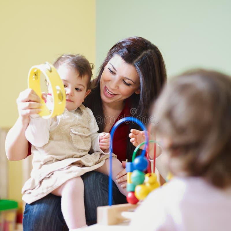 Mädchen und weiblicher Lehrer im Kindergarten lizenzfreies stockfoto