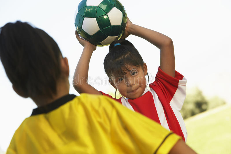 Mädchen ungefähr, zum des Fußballs zu werfen stockfotografie