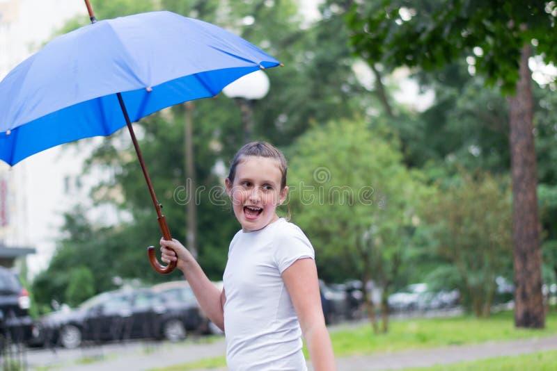 Mädchen unter blauem Regenschirm stockbilder