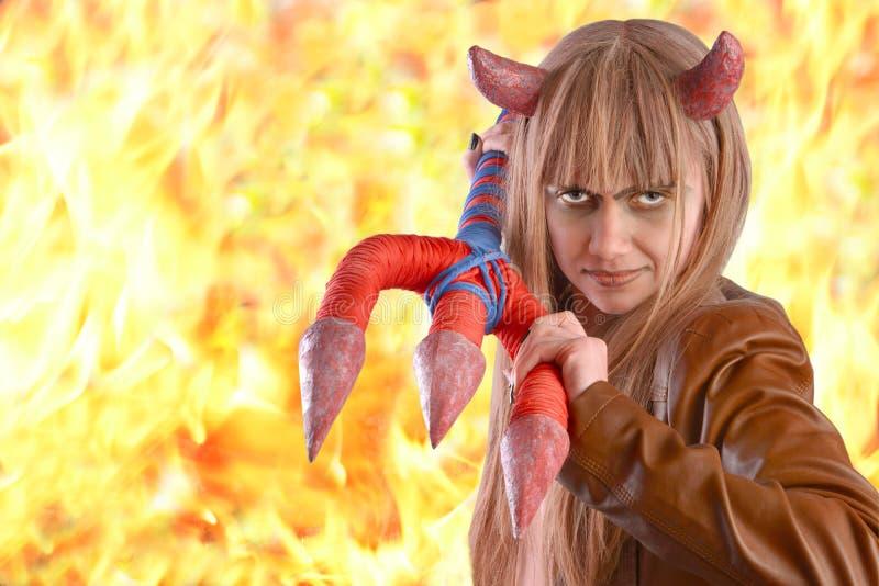 Mädchen unter dem Mantel eines Teufels auf dem Hintergrund des Feuers stockfoto