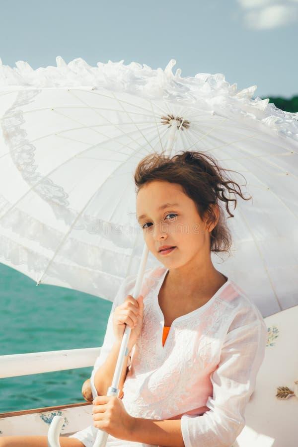 Mädchen unter einem weißen Spitzeregenschirm stockfoto