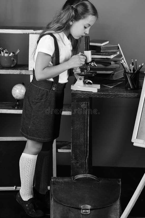 Mädchen untersucht bereitstehende Bücher und Tasche des Mikroskops Schulmädchen mit beschäftigtem Gesicht nahe Bücherregal mit Sc lizenzfreies stockfoto