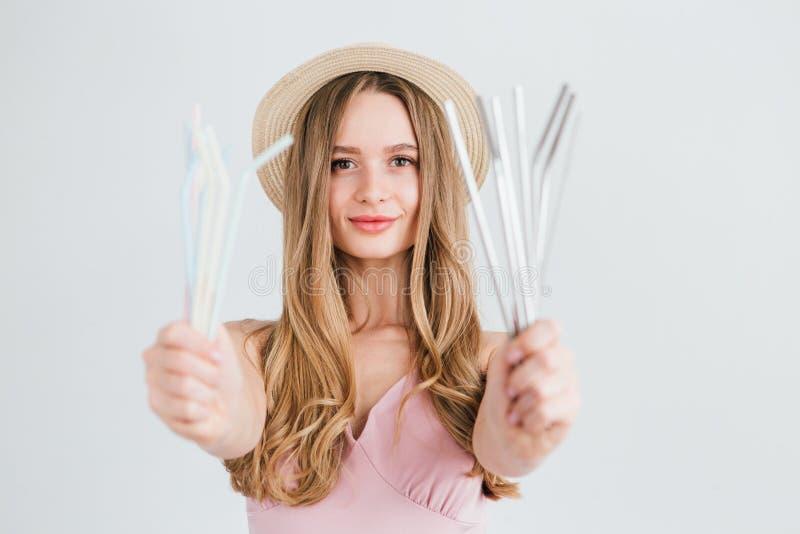Mädchen vergleicht nützliche wiederverwendbare Metallrohre für Cocktails mit schädlichem Plastik stockbilder