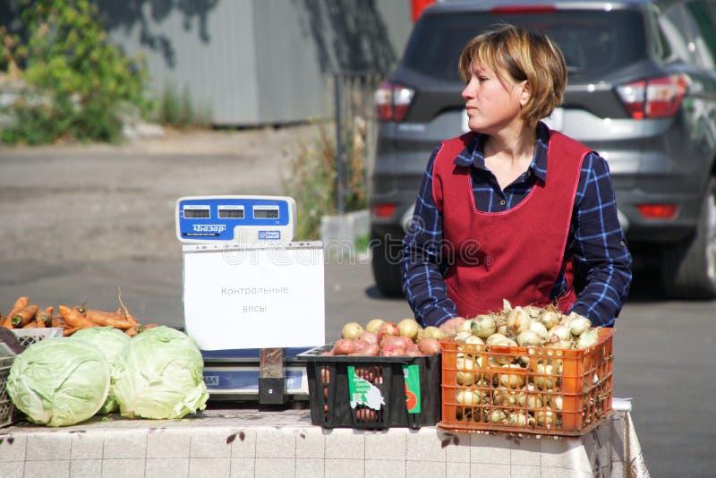 Mädchen-Verkäufer nahe bei den Skalen an der Bauernhofstraßenmesse lizenzfreie stockfotografie