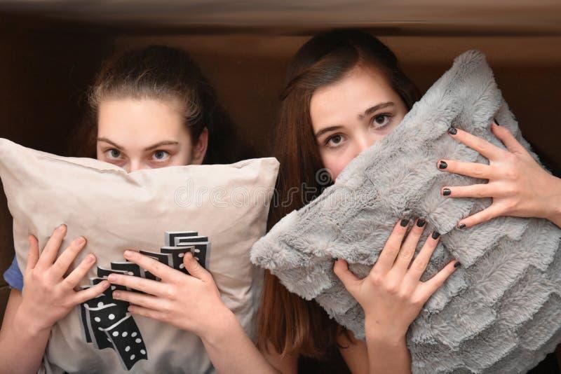 Mädchen versteckt hinter einem Kissen stockbilder